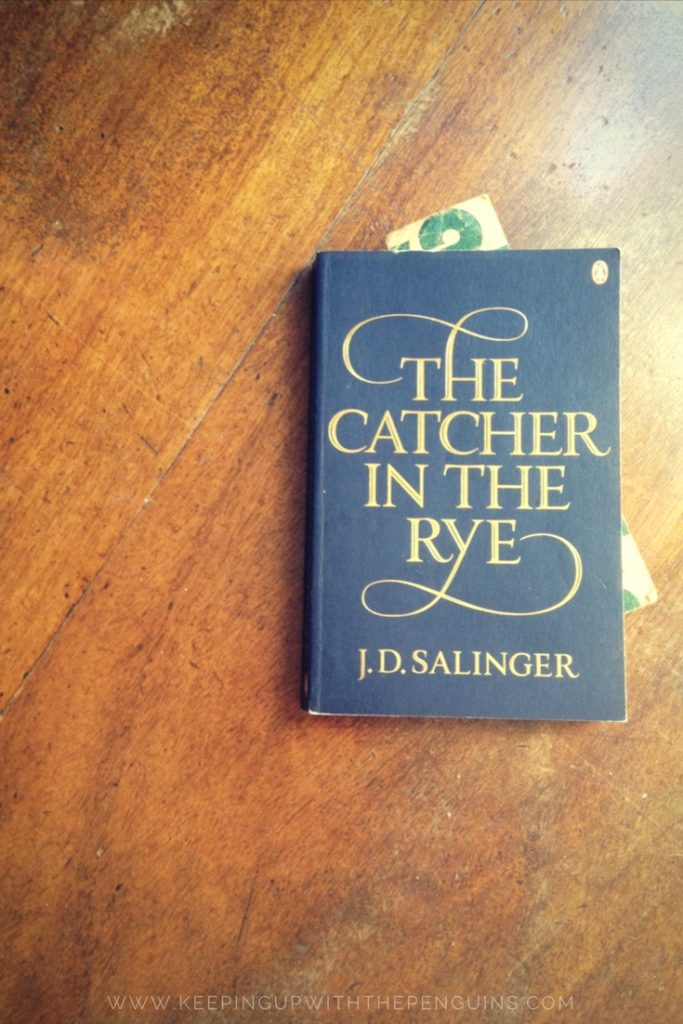The Catcher in the Rye - JD Salinger - book laid on wooden table - Keeping Up With The Penguins