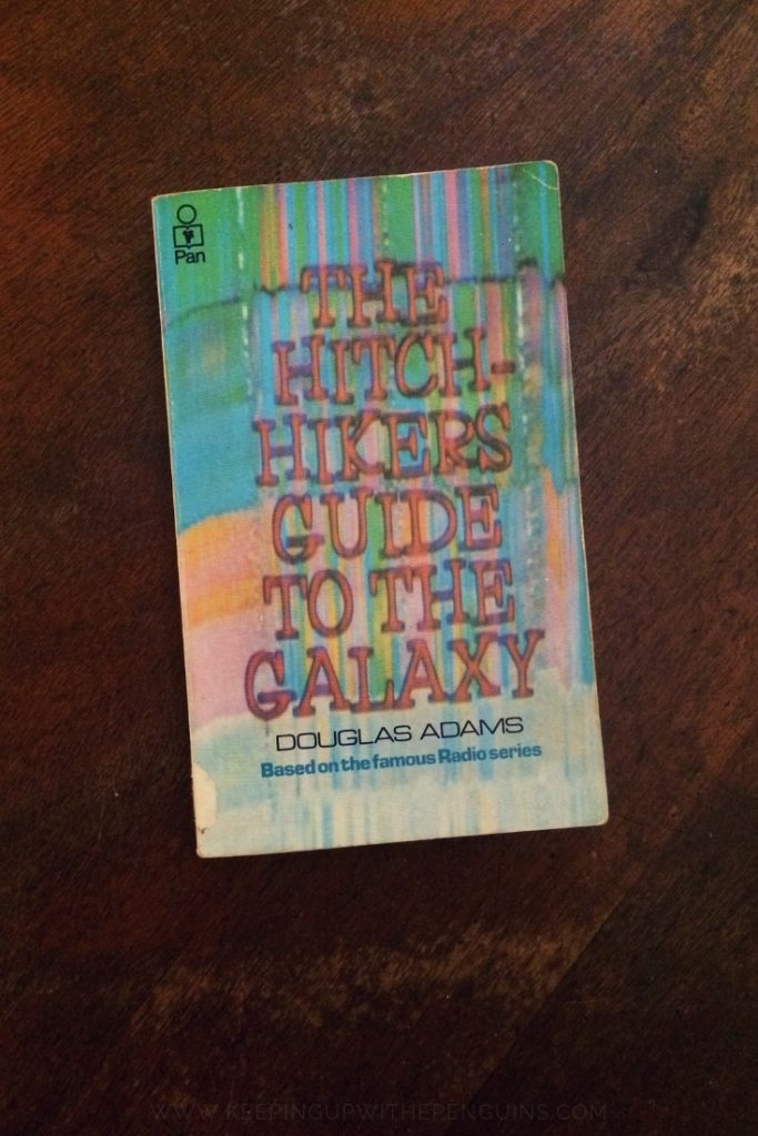 The Hitchhiker's Guide To The Galaxy - Douglas Adams - Book Laid On Wooden Table - Keeping Up With The Penguins