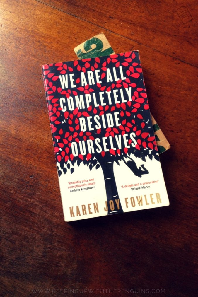 We Are All Completely Beside Ourselves - Karen Joy Fowler - book laid on a wooden table - Keeping Up With The Penguins